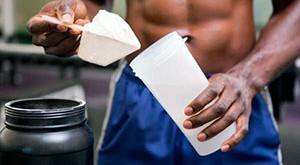 Спортсмен насыпает протеин в шейкер